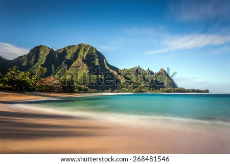 Long exposure of Makua beach or more commonly known as Tunnels Beach on the Island of Kauai. Idyllic tropical Hawaiian paradise with its tall lush mountains, turquoise sea and white sand.  - stock photo