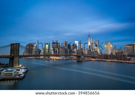 Long exposure of Manhattan Island with milky water and streaky clouds - stock photo