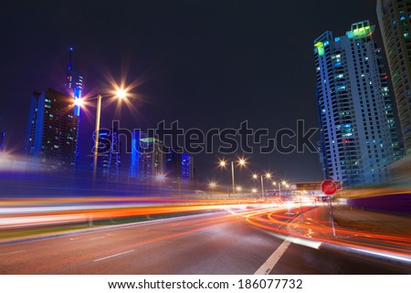 Long exposure of moving cars on night road in modern city Dubai - stock photo