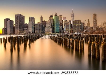 Long exposure of the Lower Manhattan skyline at sunset with an old Brooklyn pier in the foreground - stock photo