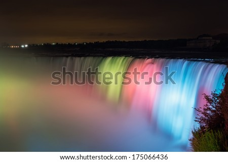 Long exposure of the rushing Niagara Falls lit up at night in different colors - stock photo
