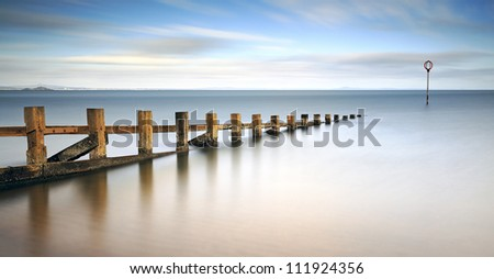 Long exposure of wooden groynes leading in to the north sea at Portobello, Edinburgh