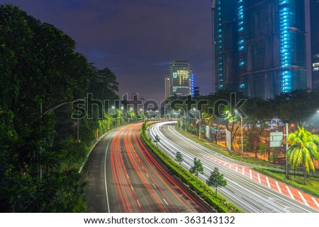 Long exposure photo of light trail from land vehicle driving through road that leads to a building and sunrise - stock photo