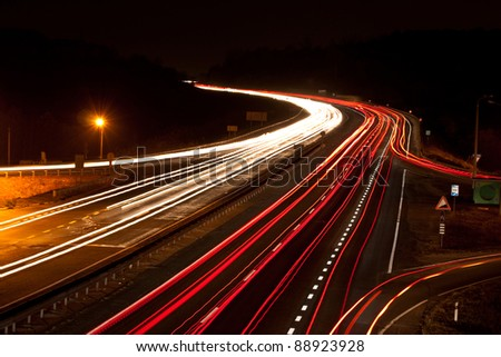 Long exposure photo of traffic on the move at dusk on the motorway - stock photo