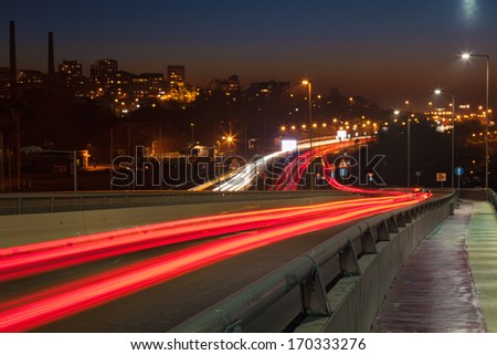 Long exposure photo on a city streets with car light trails - stock photo