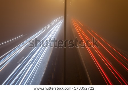 Long exposure photo on a highway with car light trails at misty night - stock photo