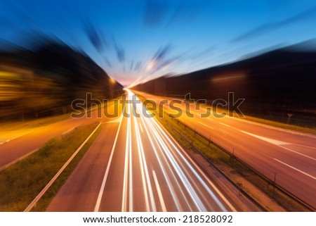 Long exposure photo on a highway with light trails at dusk in blurred motion - stock photo