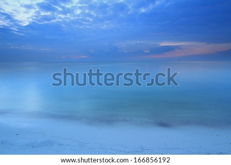 Long exposure seascape dramatic tropical sunset sky and sea at dusk