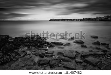 Long exposure seascape landscape during dramatic evening sunset in black and white - stock photo