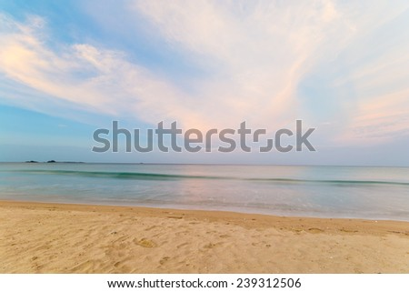 Long exposure shot at sunset from a tropical desert beach during monsoon time. Blurred sea effect, pastel colors. - stock photo