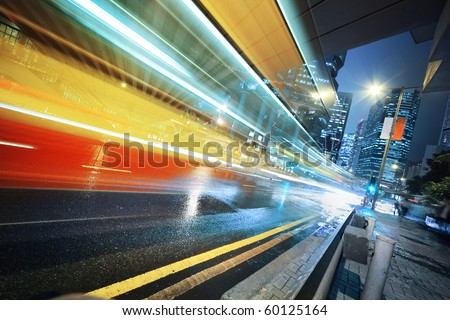 Long exposure shot of blurred bus speeding through night street. - stock photo