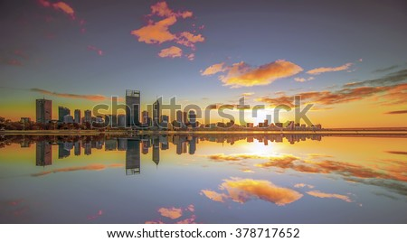 Long Exposure Shot of Golden Sunrise View of Perth Skyline from Swan River with Full Reflection. Motion Blur and Soft Focus due to Long Exposure Shot - stock photo