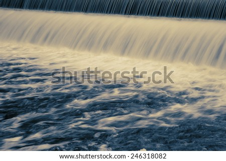 Long exposure showing water patterns of dam water flowing - stock photo