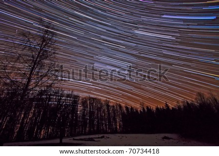 Long exposure star trails over the woods - stock photo