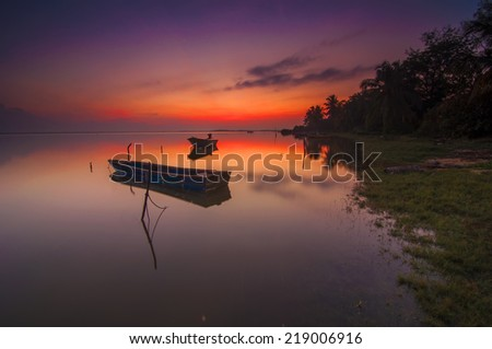Long Exposure Sunrise Seascape with Fisherman Boat on the Sea  (Soft focus, shallow DOF, slight motion blur)  - stock photo