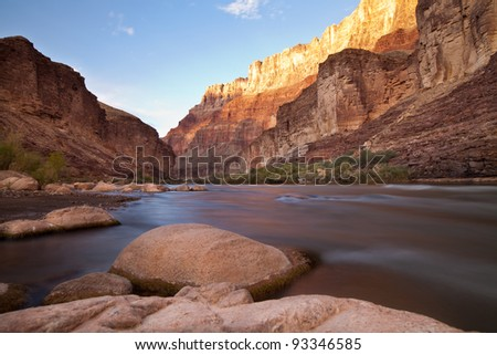 Long exposure taken from the edge of the Colorado River through the Grand Canyon at sunset - stock photo
