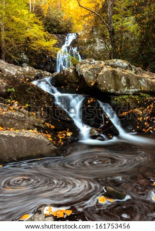 Long exposure waterfall shot, swirling leaves formation in the foreground and distant and close fall colors  - stock photo