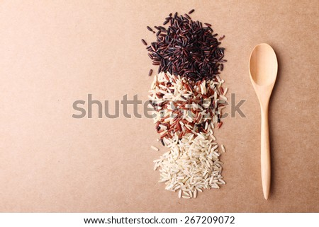 long grain rice,brown rice, with wooden spoon on brown background - stock photo