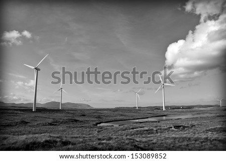 long grass and bogland with wind turbines in the background Ireland as black and white - stock photo