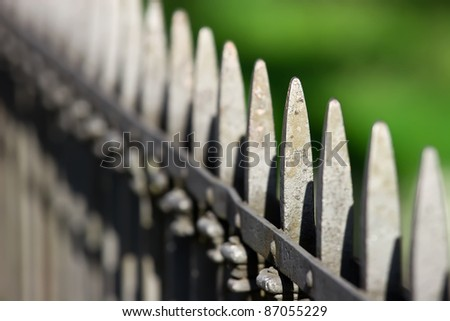 Long grey spiked fence along the road - stock photo