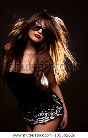long hair brunette with sunglasses dancing, studio black background - stock photo