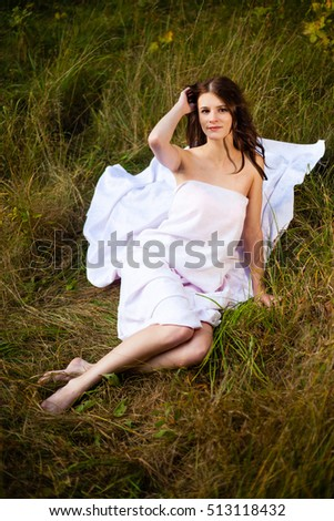Long hair girl in a  cloth on grass.