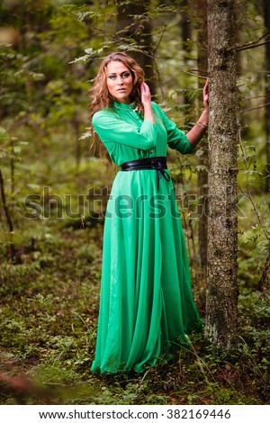 Long-hair girl in green dress at forest. - stock photo