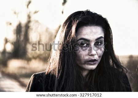 Long hair girl with scary makeup outdoor - stock photo