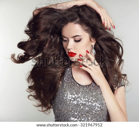 Long hair. Makeup. Beautiful girl portrait. Brunette fashion woman with red lips, manicured nails, healthy curly shiny hairstyle posing on studio background. - stock photo