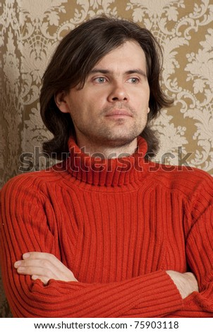 Long hair man staying against wall - stock photo