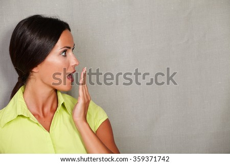 Long hair woman with hand to mouth while looking shocked away in green blouse and hair back on grey texture background - copy space