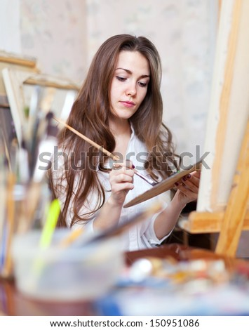 Long-haired artist paints on canvas in workshop - stock photo