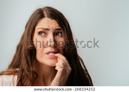 long-haired beautiful brunette girl bites his nails - stock photo