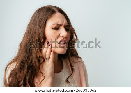 long-haired beautiful brunette girls have a toothache - stock photo