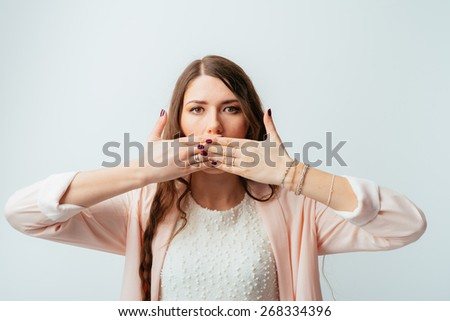 long-haired beautiful girl covers her mouth with her hands, isolated on white background - stock photo