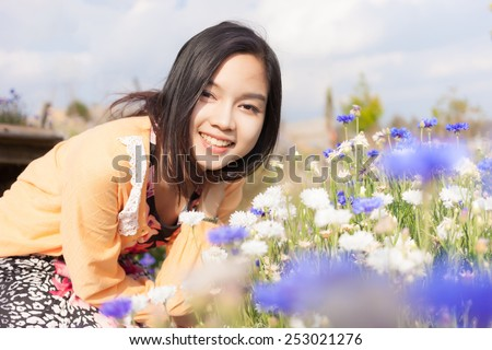 Long haired black asia girl happy smile in the flowers garden . - stock photo