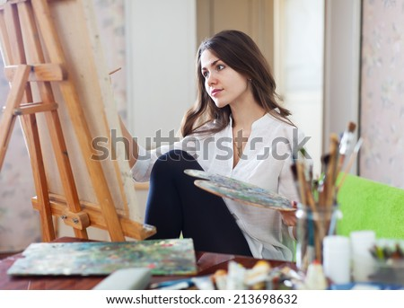 Long-haired female artist paints picture on canvas with oil paints  - stock photo