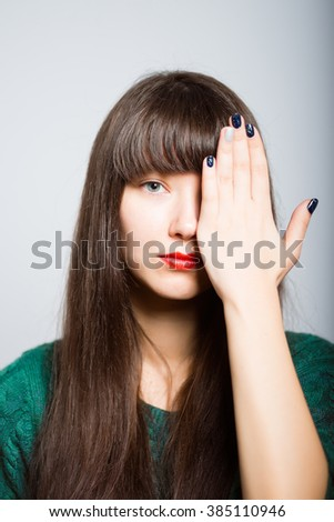 long-haired girl close one eye, an ophthalmologist, a student in isolation on a gray background - stock photo
