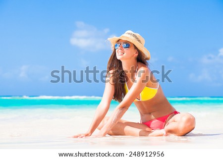 long haired girl in bikini  and a hat on tropical barbados beach - stock photo