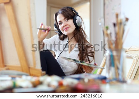 Long-haired girl in headphones  paints  on canvas in workshop interior - stock photo