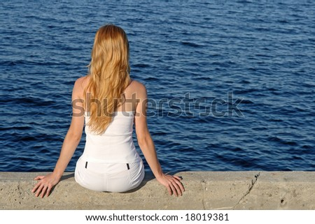 Long haired girl in white summer clothes sitting by the sea. - stock photo