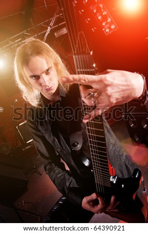 Long haired guitarist is playing and and making a rock hand gesture - stock photo