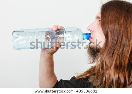 Long haired thirsty man holding bottle of water. Drinking guy.