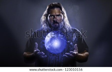 Long haired white male with a mystical glowing orb to signify power, magic, spirituality and so forth - stock photo