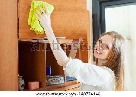 long-haired woman cleaning furniture at home - stock photo