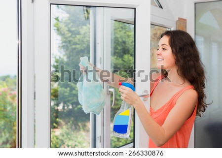 Long-haired woman cleaning windows with spray in home and smiling - stock photo