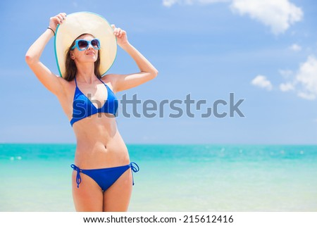 long haired woman in bikini and straw hat tanning on tropical beach - stock photo