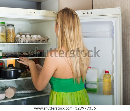 Long-haired woman looking for something in refrigerator  at home - stock photo