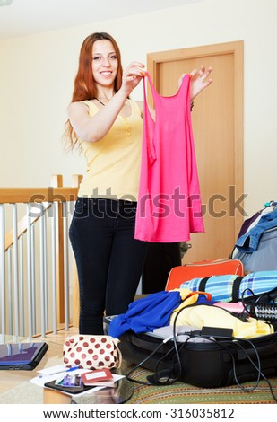 Long-haired woman packing suitcases at home going on holiday - stock photo