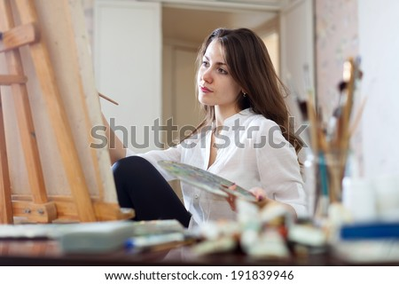 Long-haired woman paints picture on canvas with oil paints in her studio - stock photo